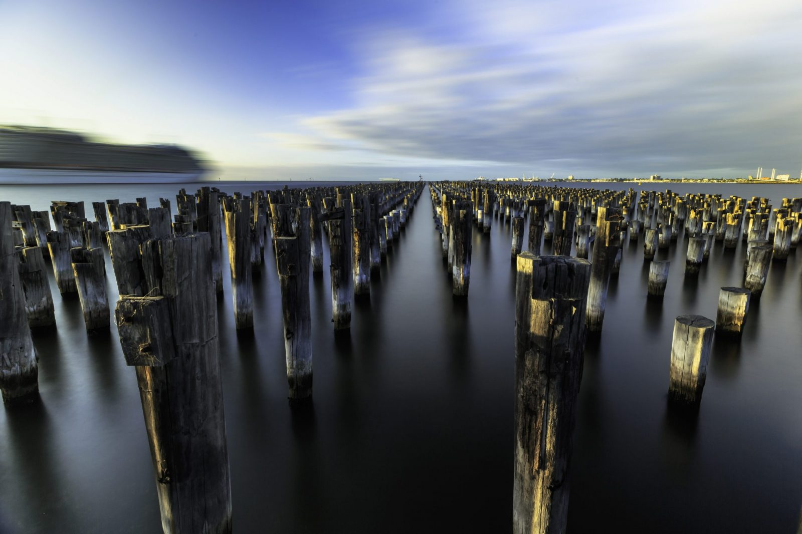 Long exposure of the wooden pillars at Princes Pier during sunrise.